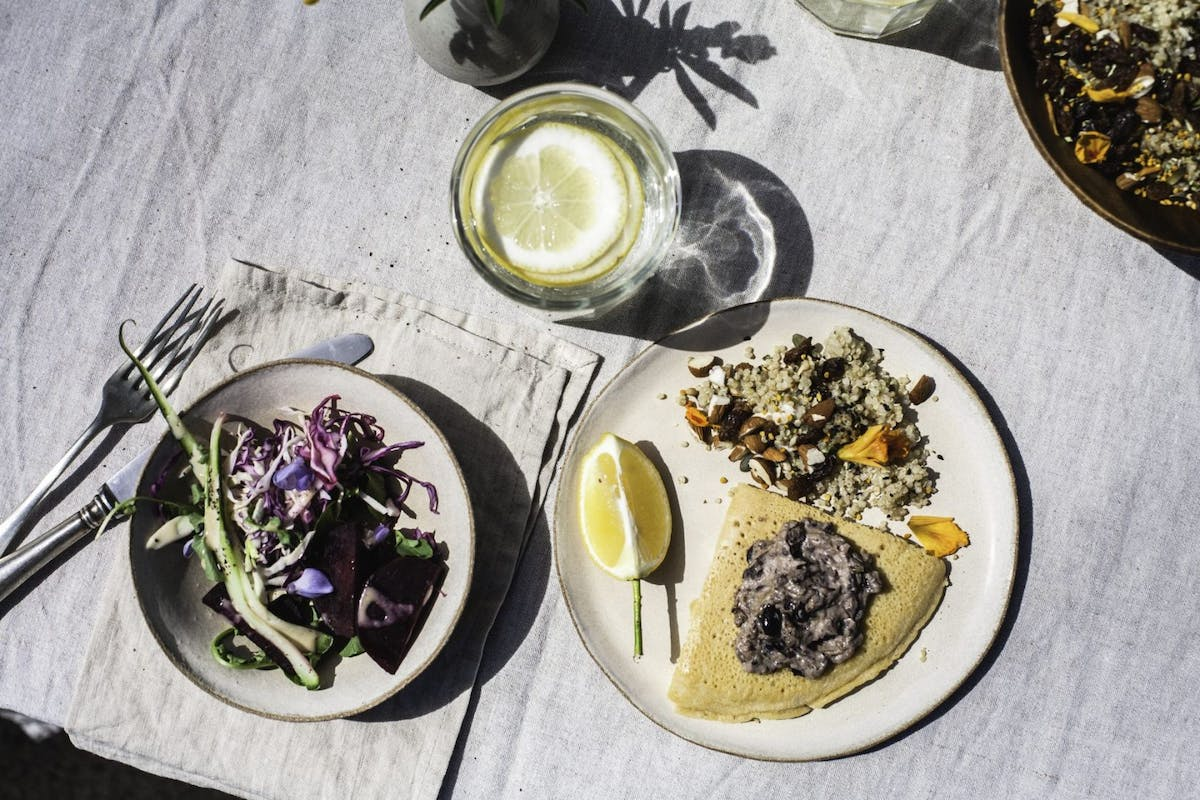 A flatlay of a salad, tortilla wrap and a glass of water on a table.