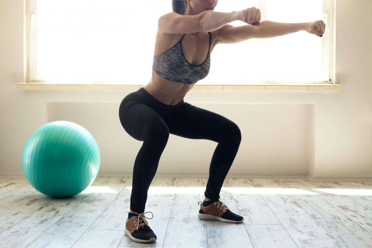 Woman doing squats at home