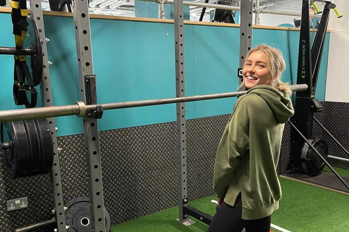 Stylist fitness writer Chloe Gray next to a squat rack with a barbell.
