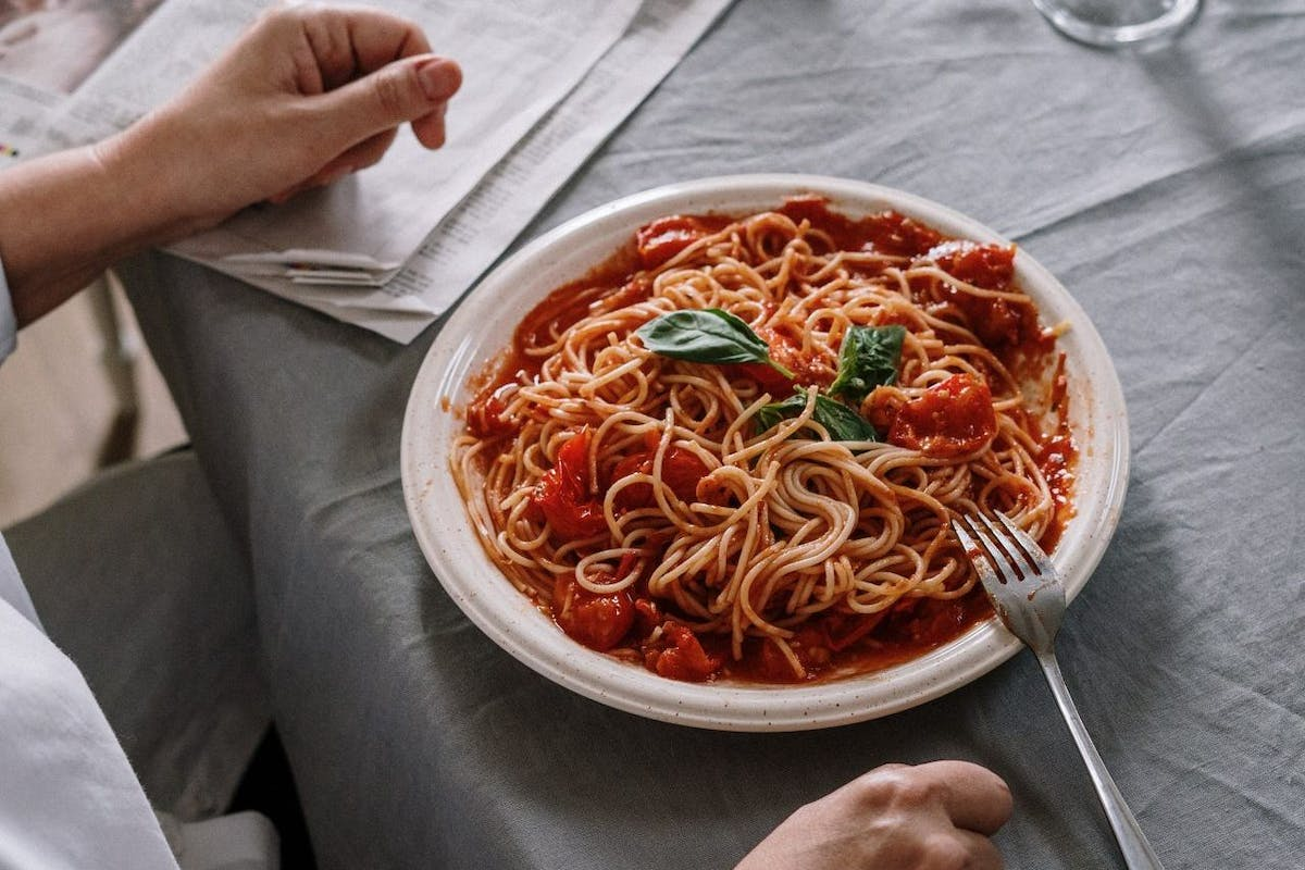 An overhead shot of a woman with a bowl of pasta