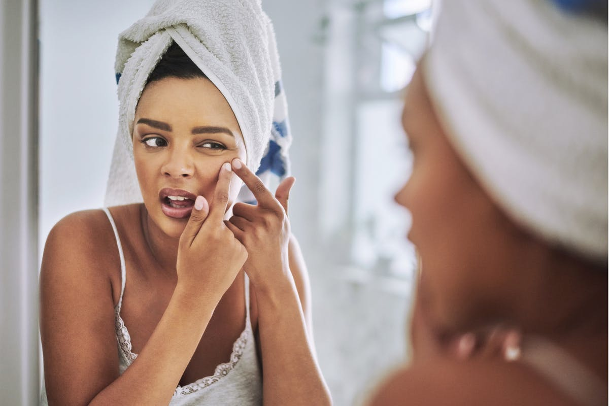 Woman picking spot on skin in mirror