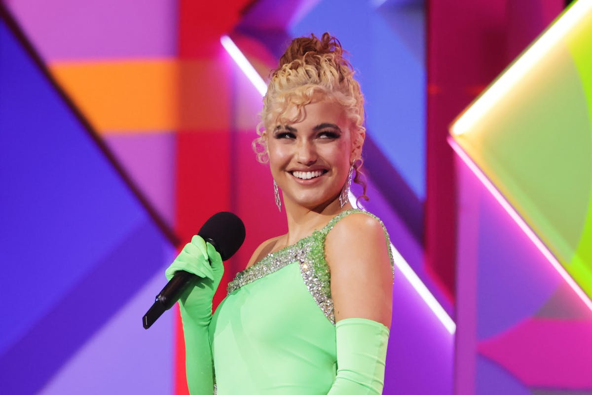 Mabel on stage at the Brit Awards 2021 with blonde curly hair and bright green dress