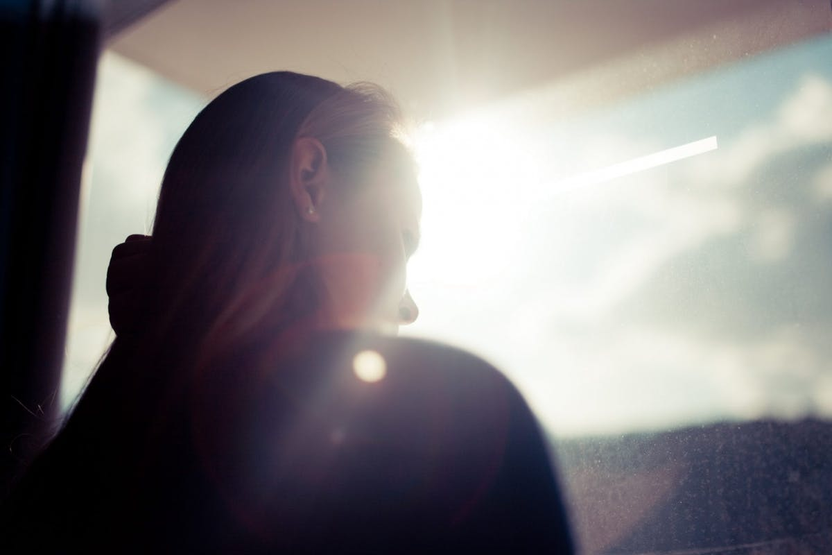 A woman looking out the window on a sunny day