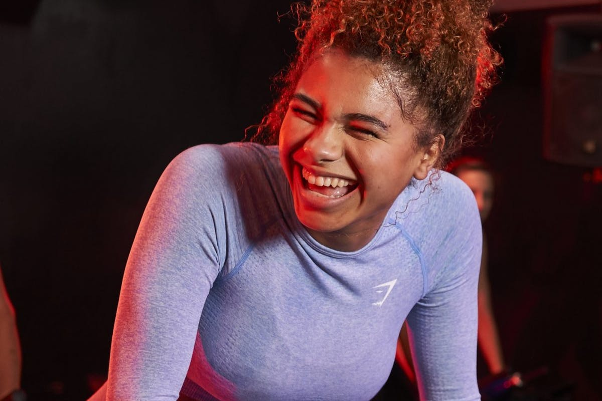 A woman on a spin bike laughing in gym activewear.