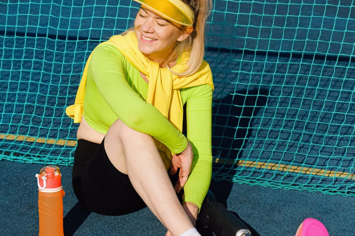 A woman sat on the floor of a tennis court in tennis wear including a visor and trainers surrounded by a tennis racket and tennis balls