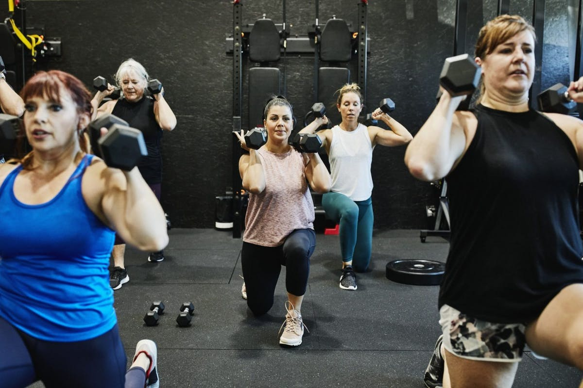 Women in a gym class doing a lunch with dumbbells on their shoulders.