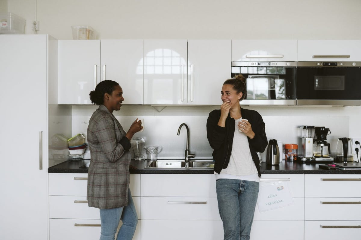 Two women chatting in the kitchen at work