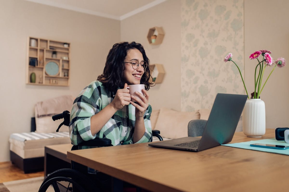A woman in a wheelchair working from home