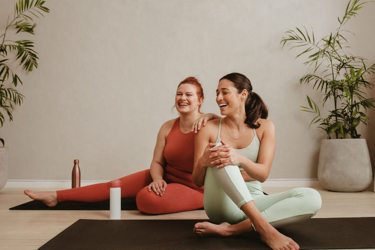 Two women sat on the gym floor stretching their bodies