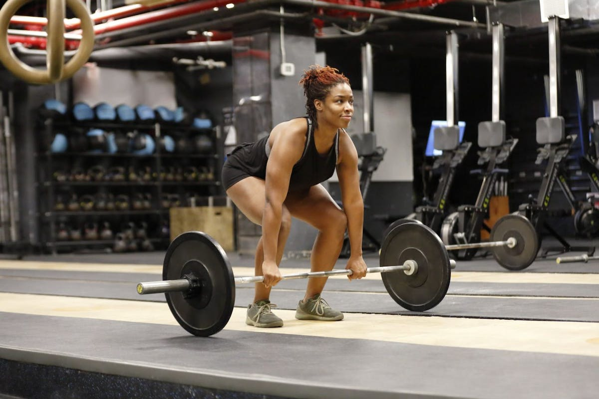 A woman gripping a barbell on the floor about to do a deadlift
