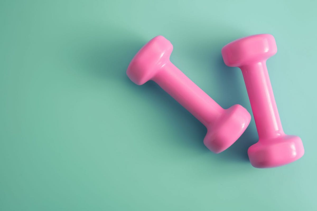 Two pink dumbbells on a green background.