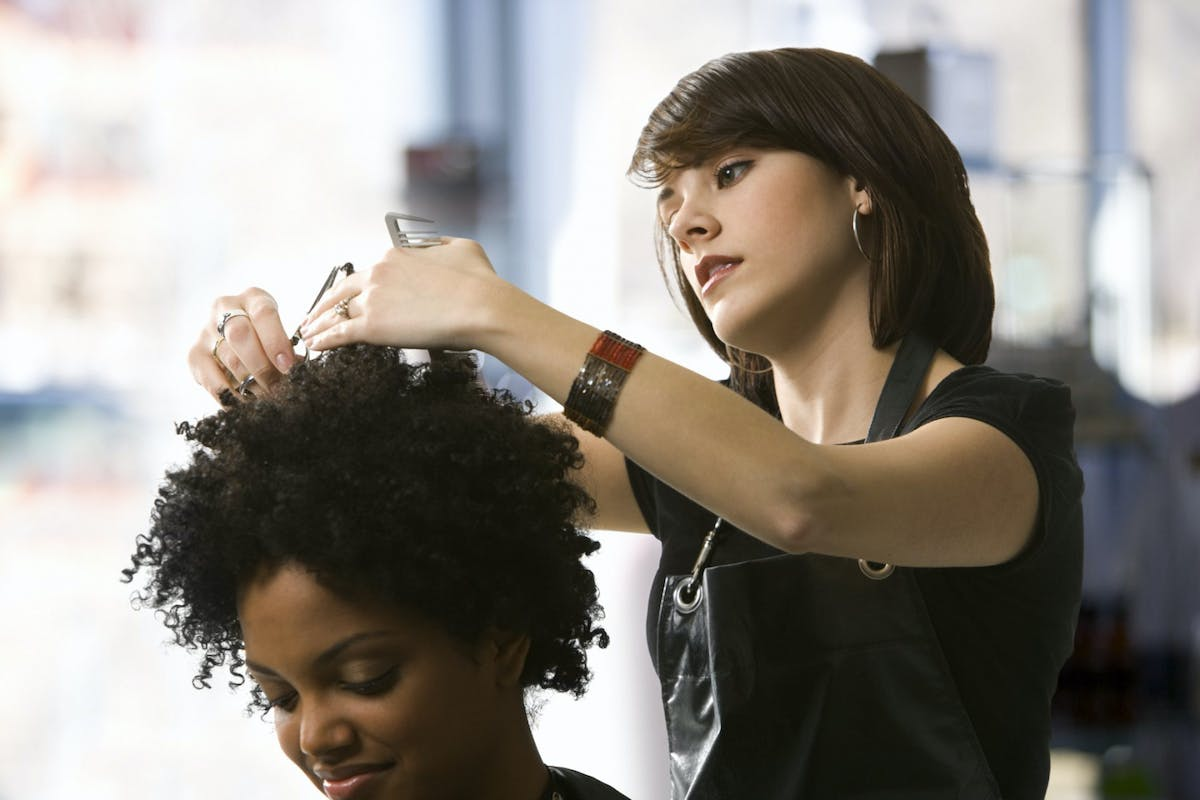 Black woman getting a haircut from a white hairdresser