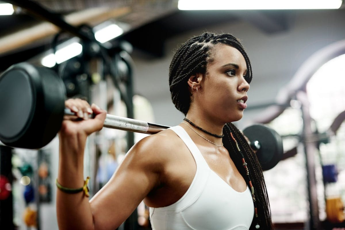 A woman in the gym with a barbell on her back