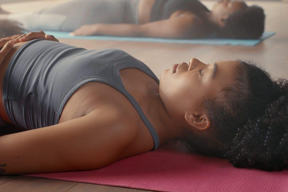 A woman doing shavasana lying on her yoga mat