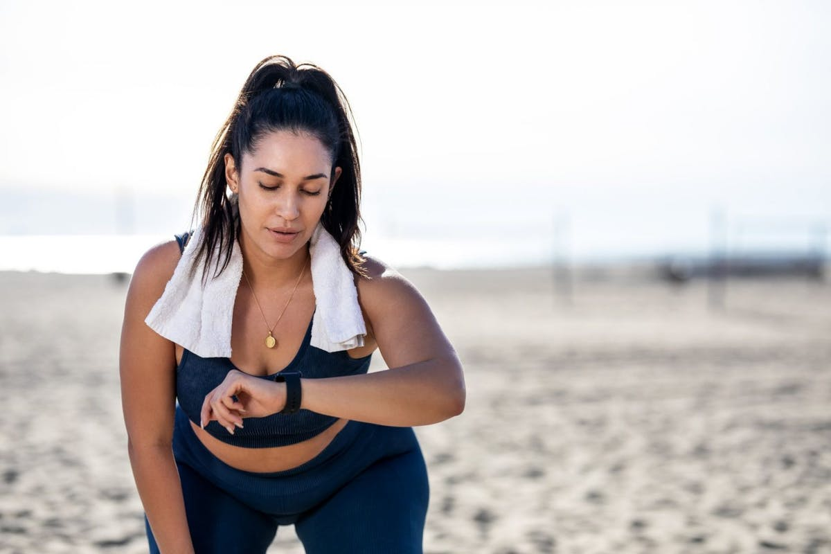 A woman exercising on a beach checking her smart watch.