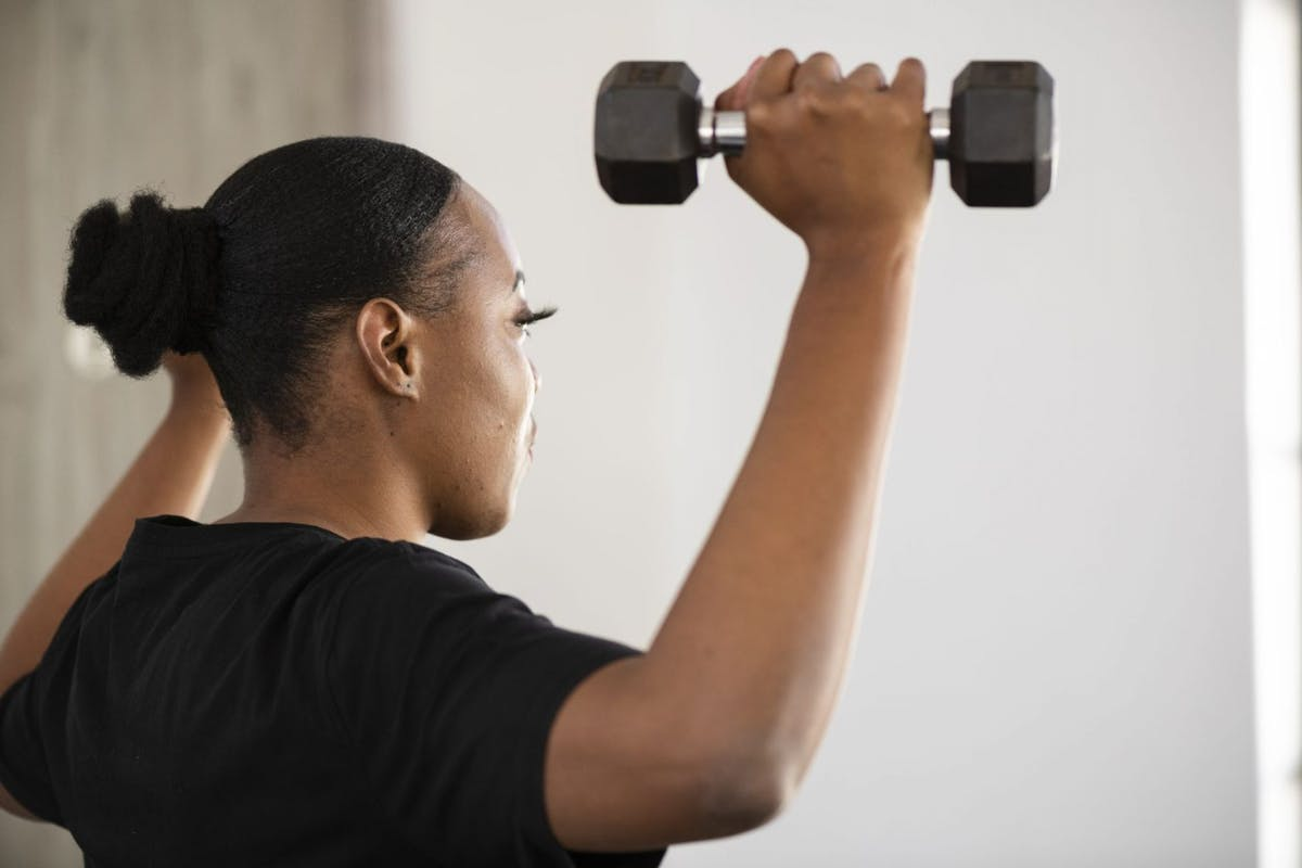 A woman with dumbbells in he rhand