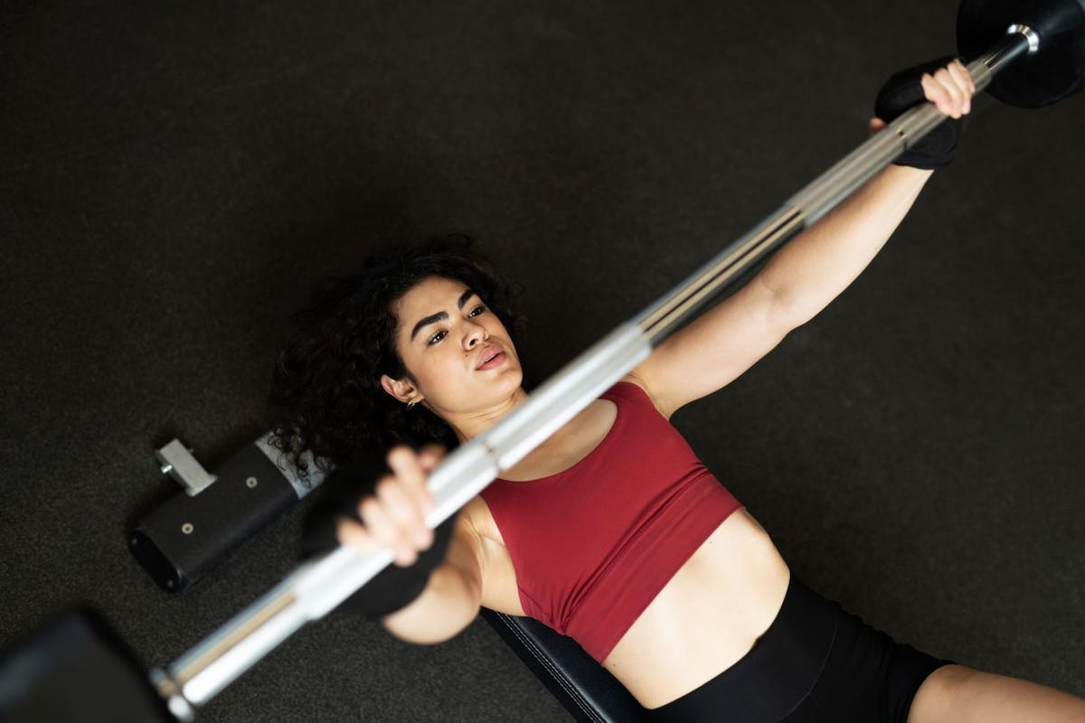 A woman doing a bench press with a barbell overhead