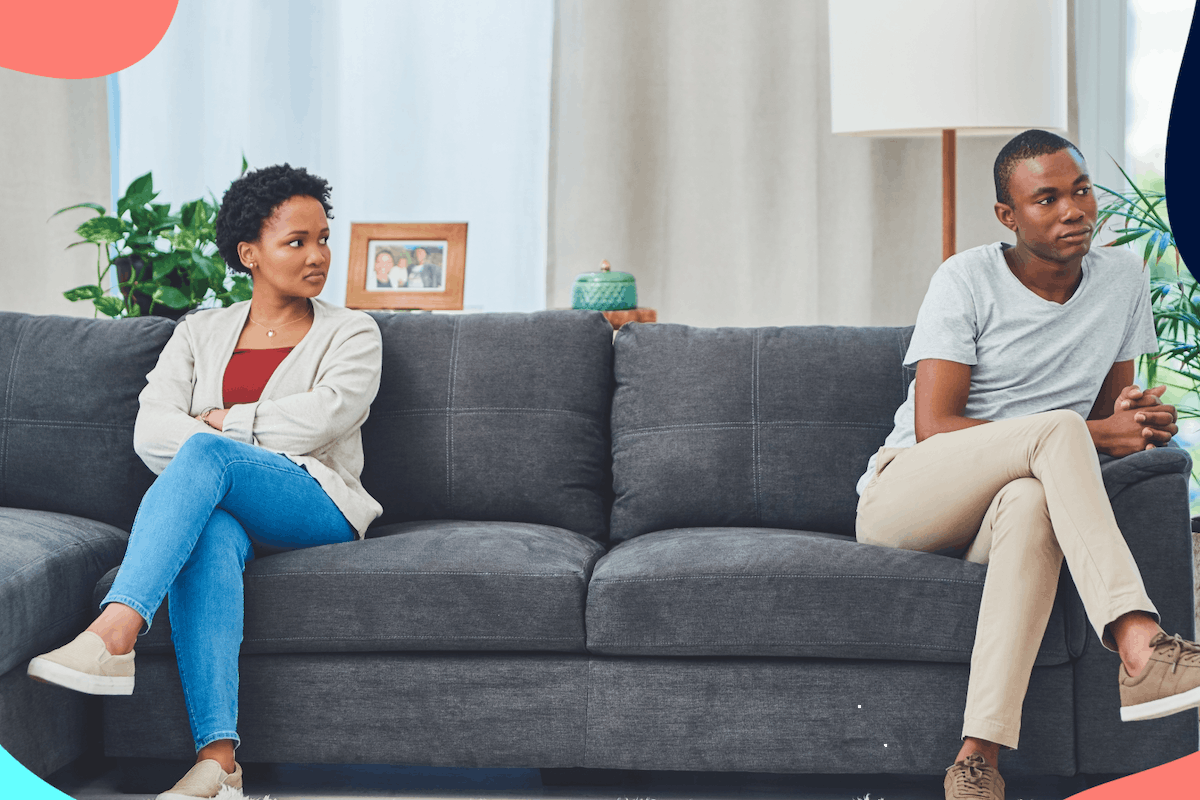 couple sat on opposite ends of couch arguing
