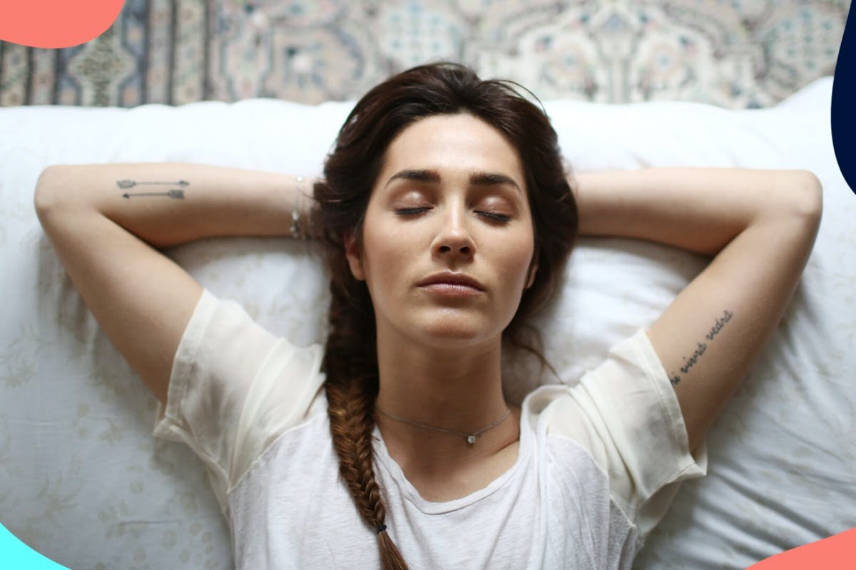 Woman with dark hair laying back on a bed, relaxing with her eyes closed.