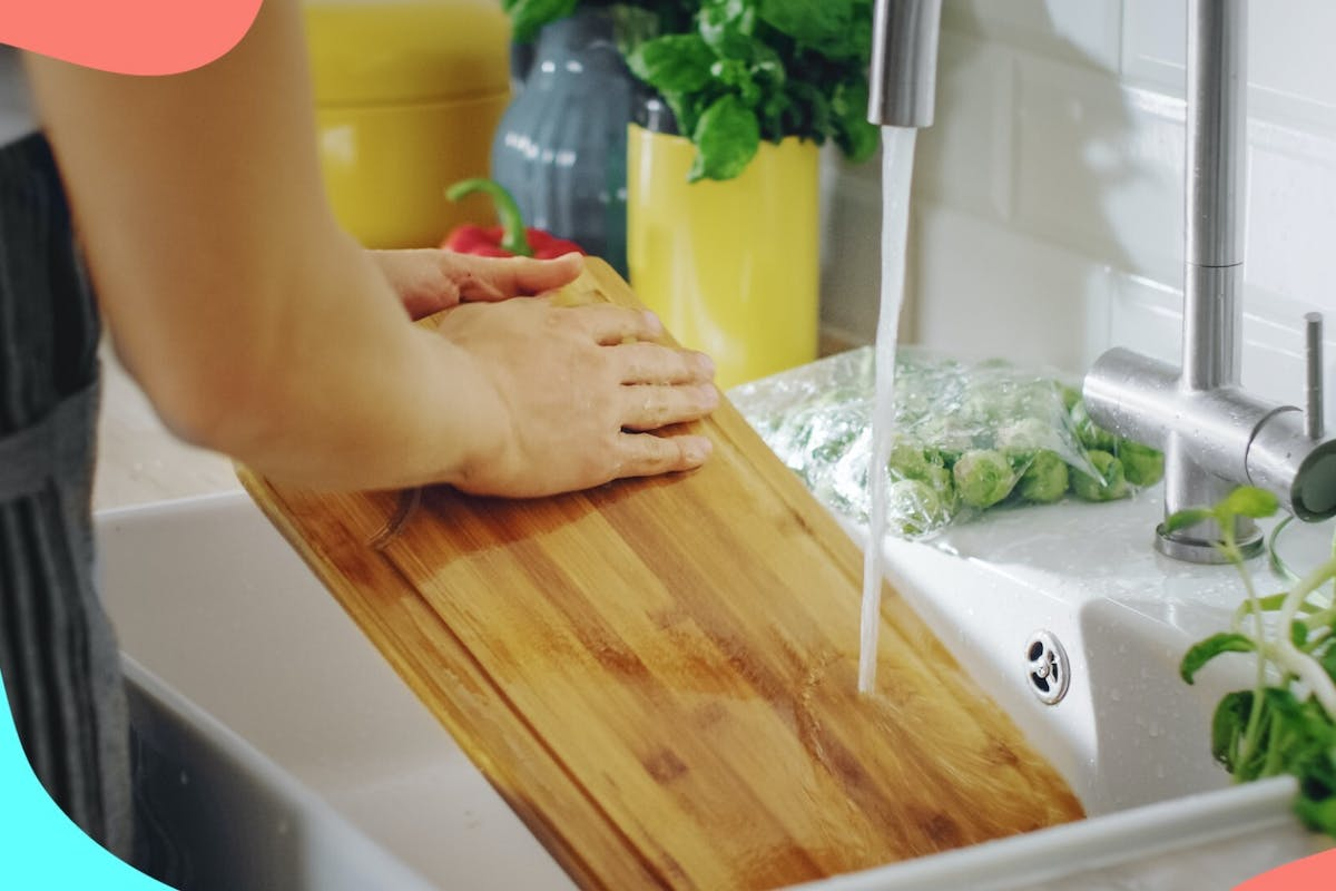 Woman washing chopping board under tap at a kitchen sink.