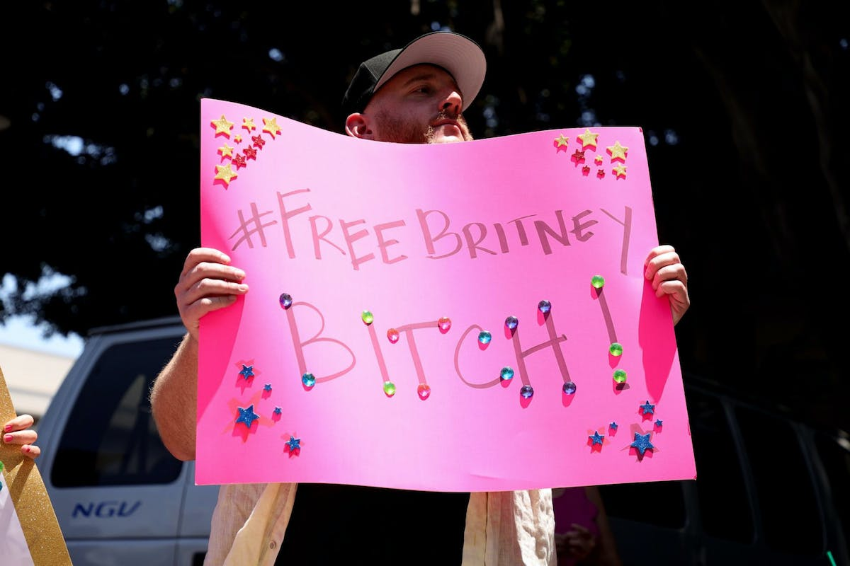 """A man holding a sign that says """"#FreeBritney bitch"""""""