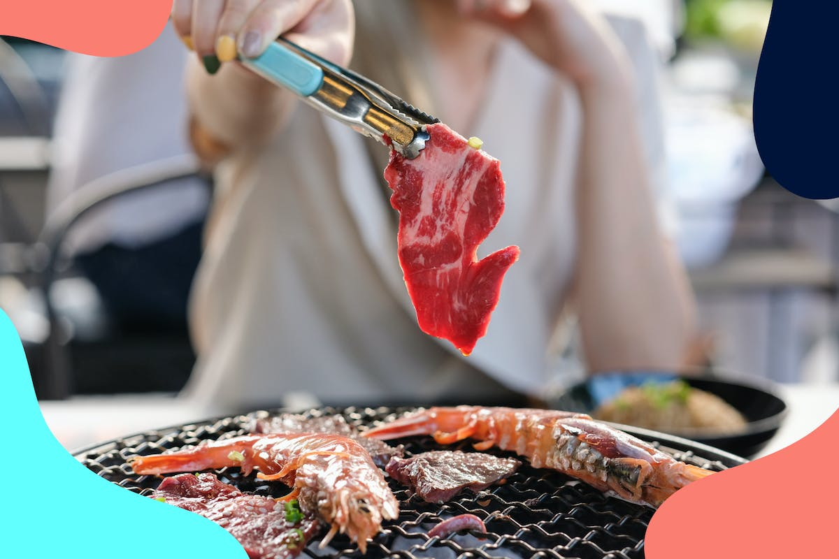 Woman holding tongs over barbecue