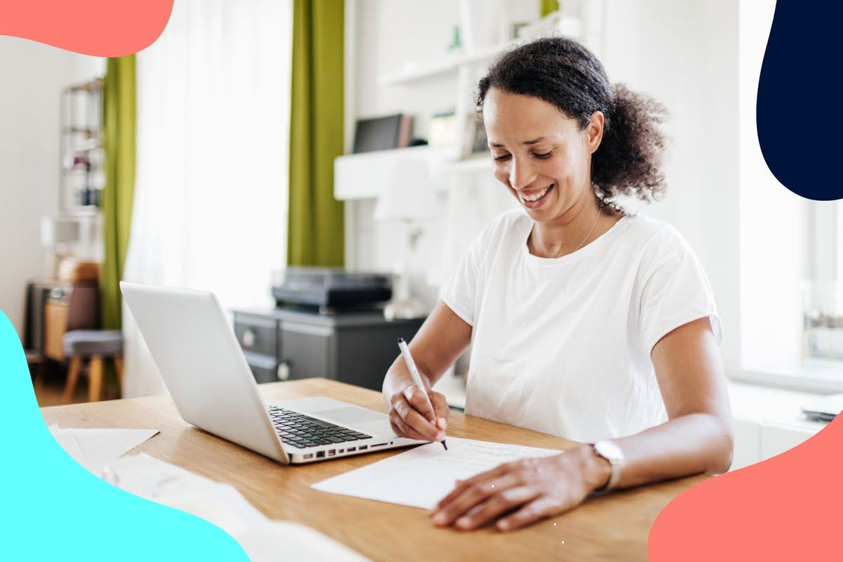 woman working at laptop and writing in notebook