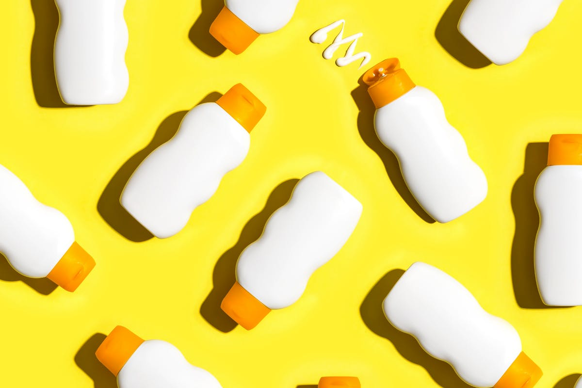 Sunscreen bottles on a yellow background