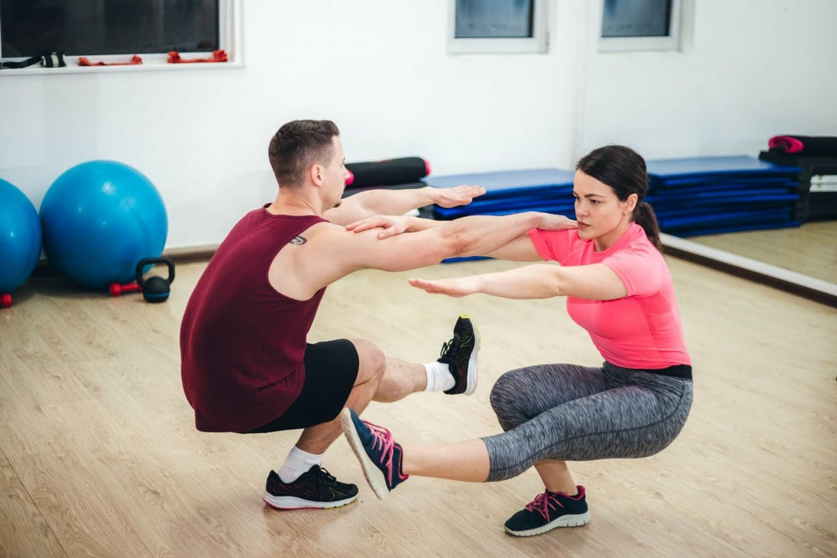 A woman and man doing supported pistol squats