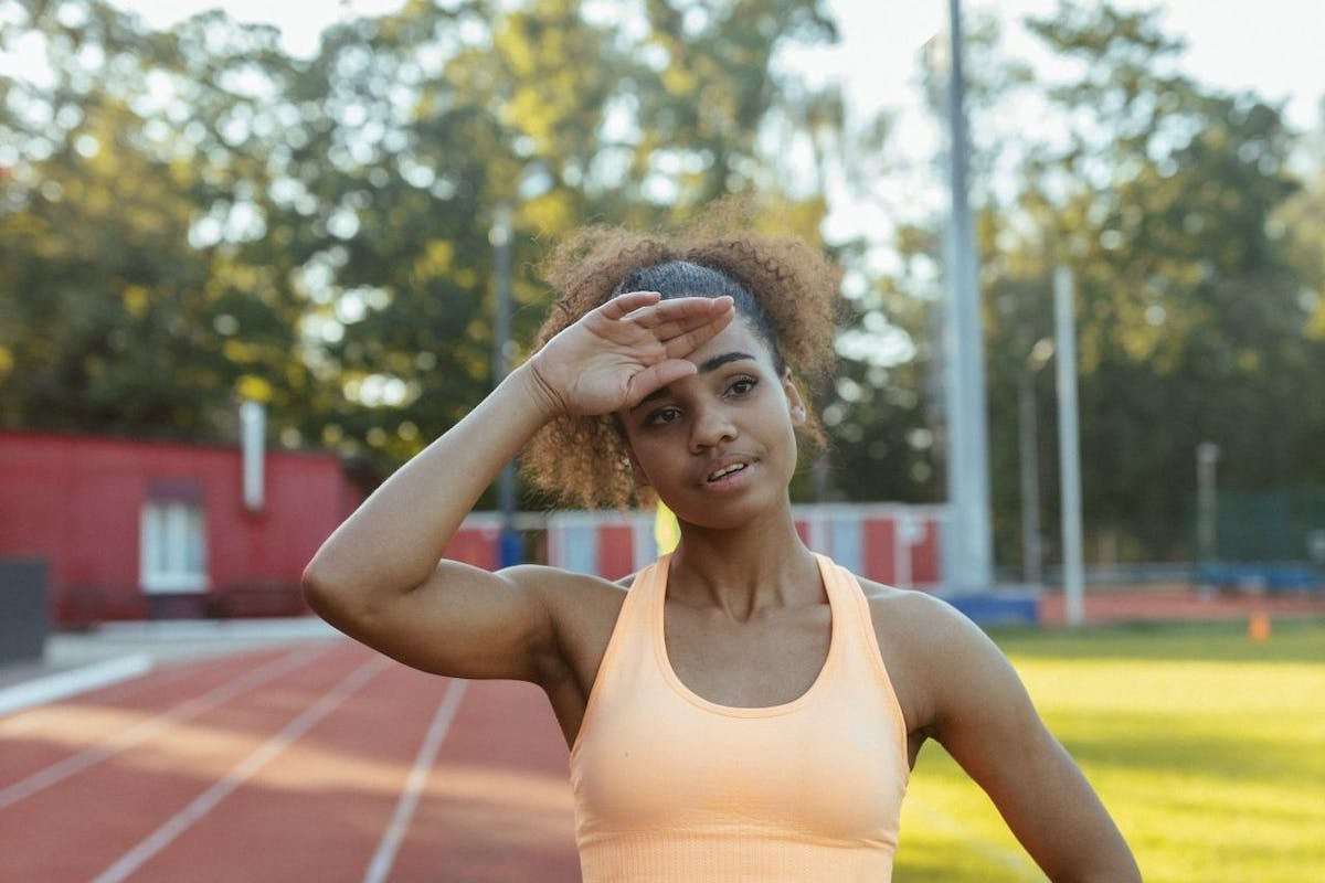 A woman on a race track wiping her forehead