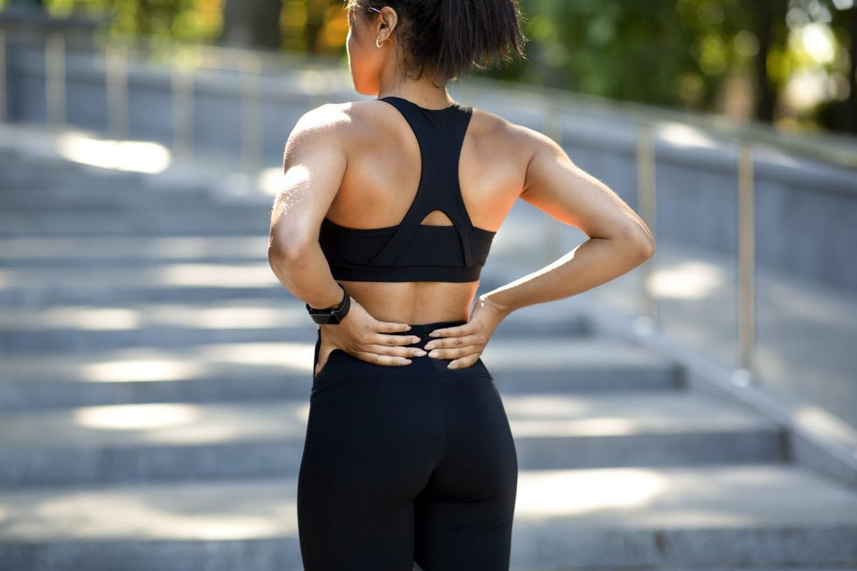A woman holding her back with an exercise injury.