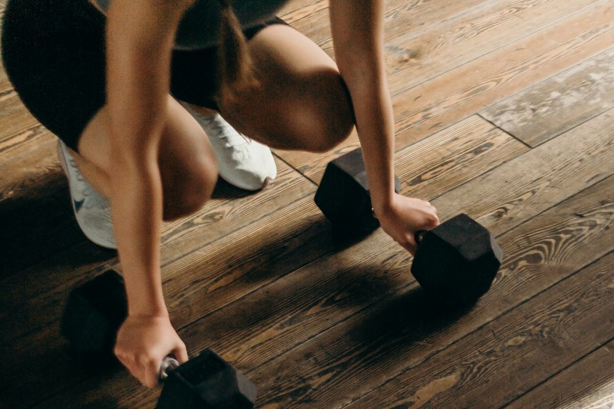 A woman leaning on dumbbells in the gym