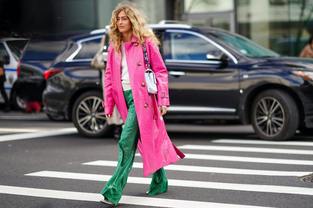 Blonde woman crossing street wearing bright pink coat and green trousers.