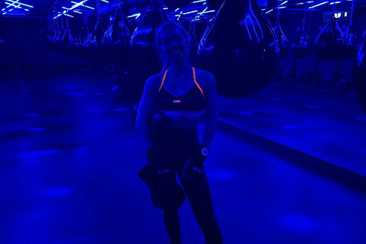 Chloe at Kobox, in a dark boxing studio with blue light wearing boxing gloves
