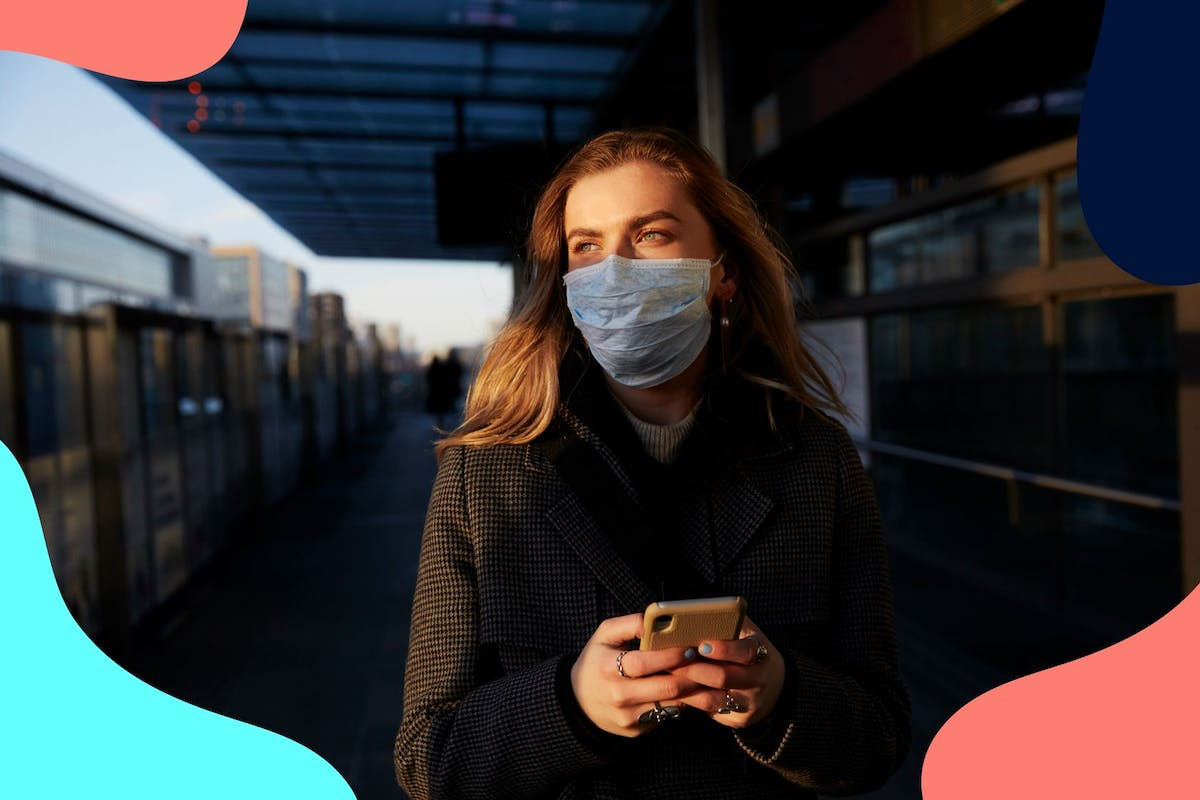 woman wearing face mask on phone at train station