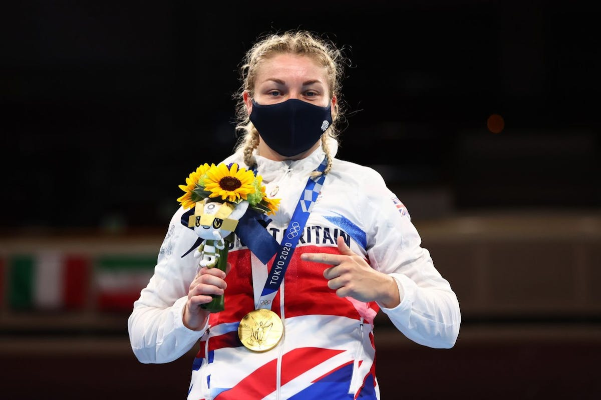 Lauren Price on the podium with flowers anda gold medal