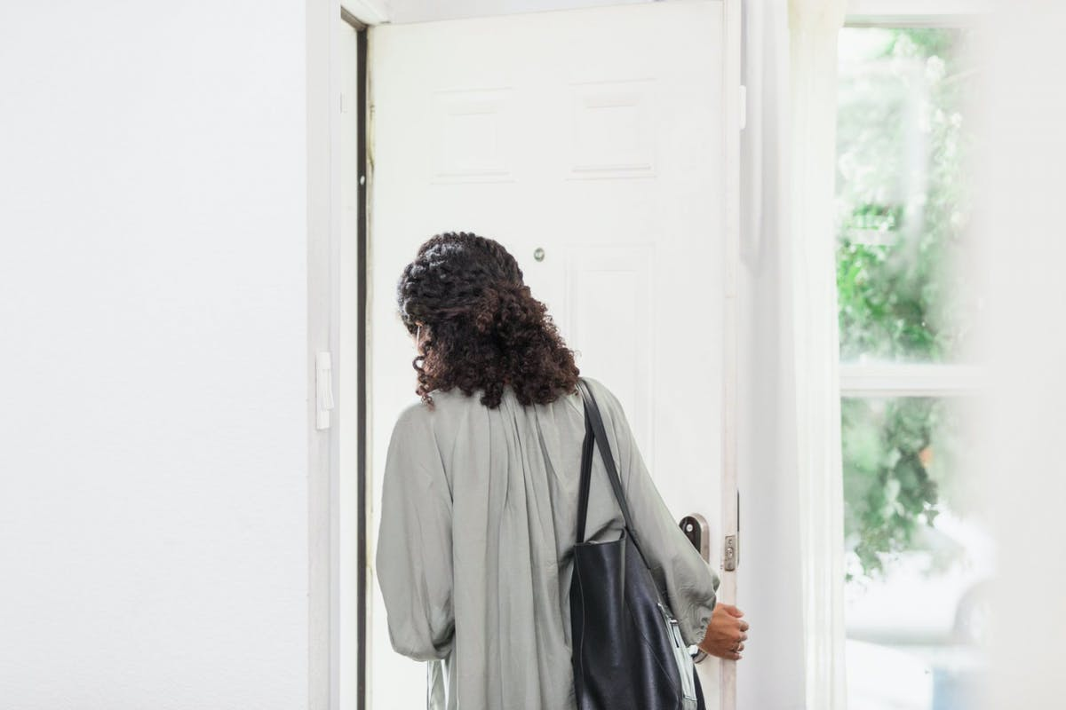 A woman walking out the door on her way to work