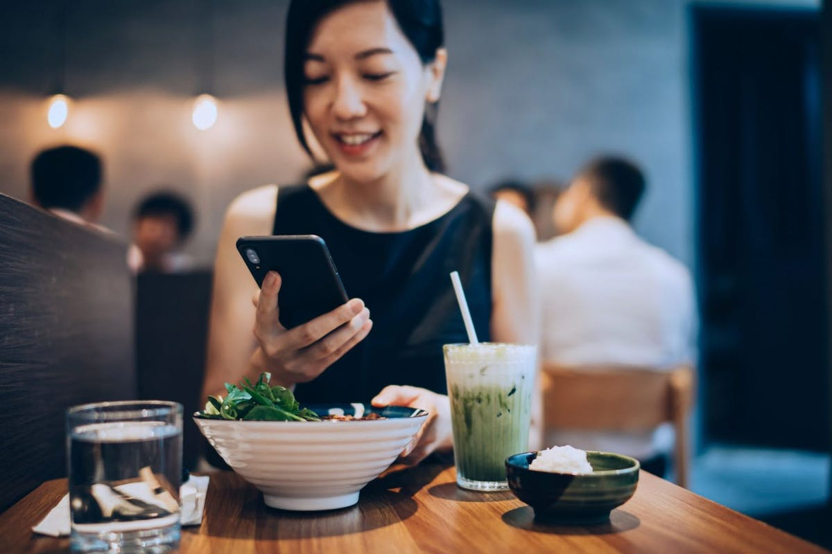 A woman with a salad and a smoothie logging her calories in her phone