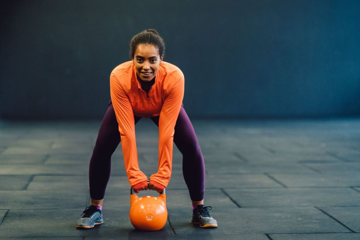 A woman in the gym swinging a kettlebell