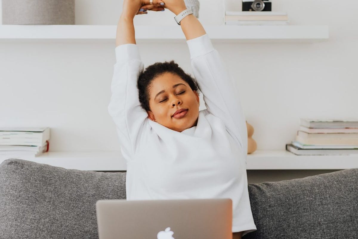 A woman sat on the sofa with a laptop on her legs stretching arms overhead
