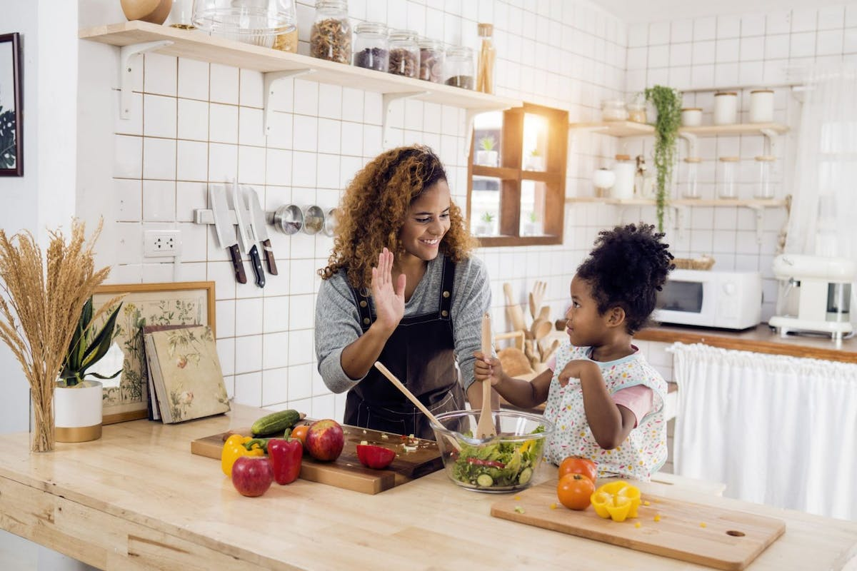 A mum and daughter cooking healthy food in the kitchen