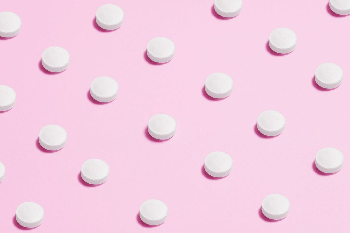 Lots of contraceptive pills on a pink background
