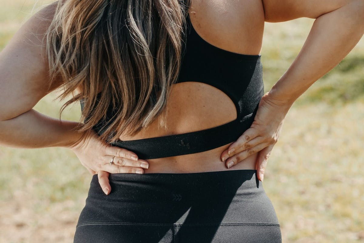 A woman photographed from behind in activewear gripping her back