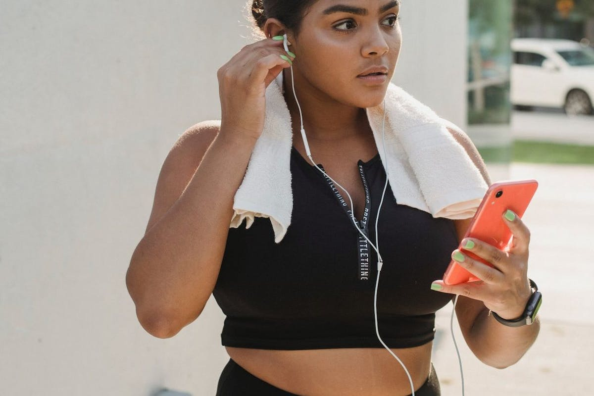 A woman in activewear with a towel around her neck putting headphones in before she goes for a run