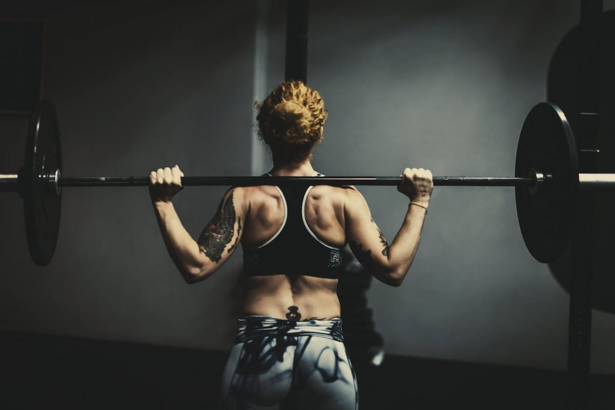 A woman with a barbell on her back doing a squat
