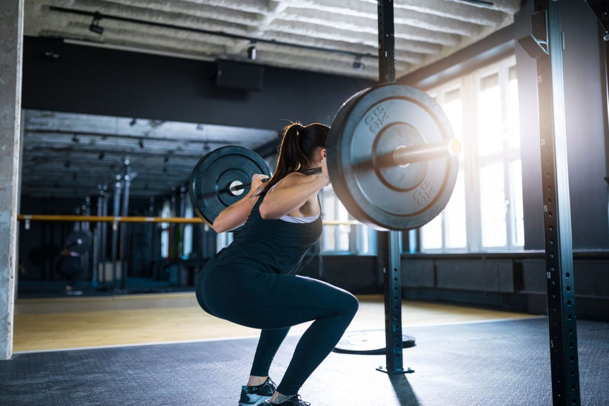 A woman doing a squat with a barbell on her back using a power rack in a gym