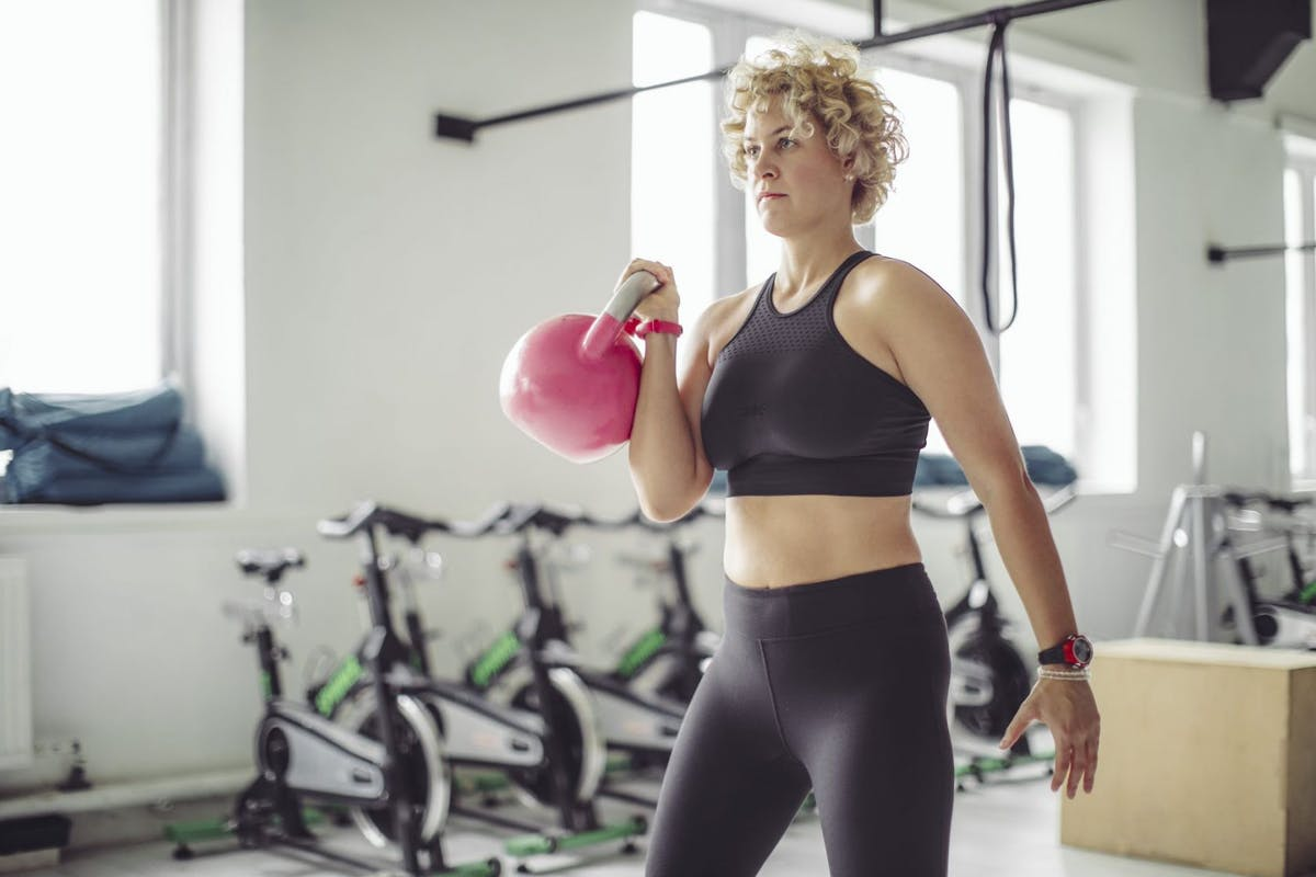 A woman with a kettlebll in her hand in the gym