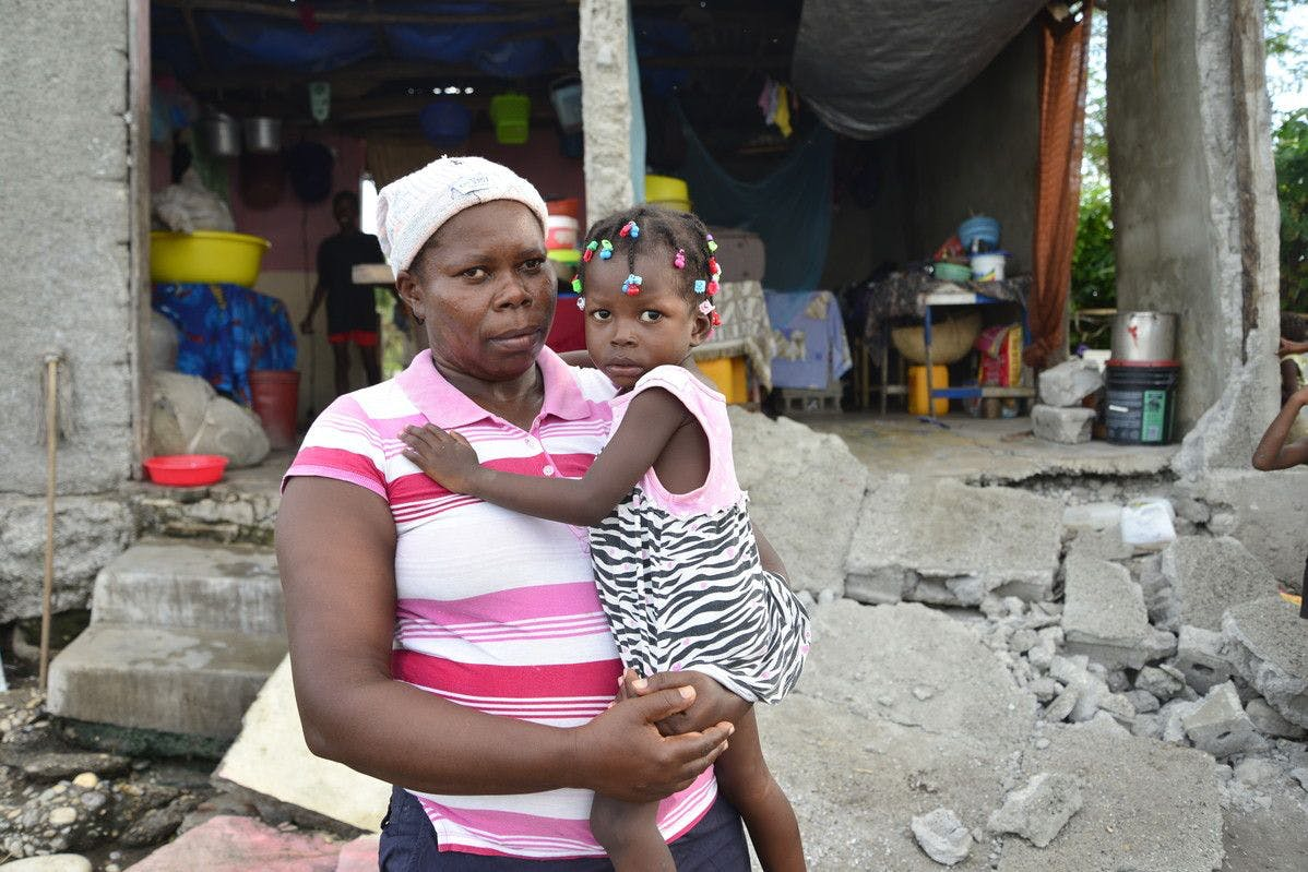 A mother and daughter stand in front of their ruined home