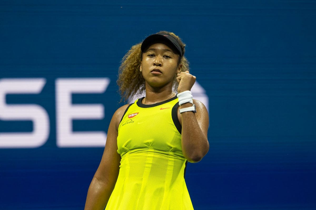 Naomi OSaka at the 2021 US Open in a bright yellow dress and black cap