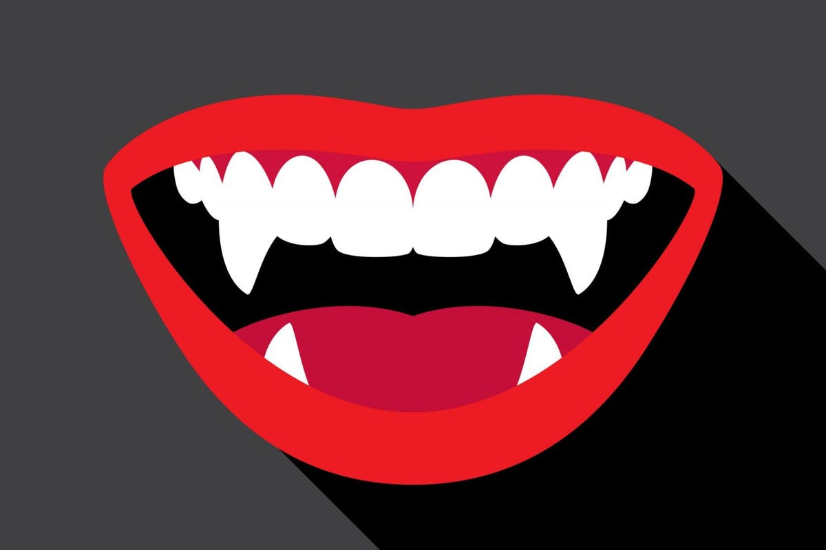 Vector illustration of a a mouth with vampire fangs against a black background.